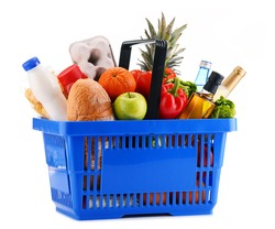 Plastic shopping basket with assorted grocery products isolated on white