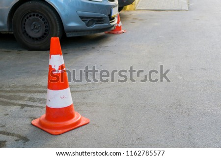 Plastic signaling traffic cone encloses a place in the parking lot  #1162785577