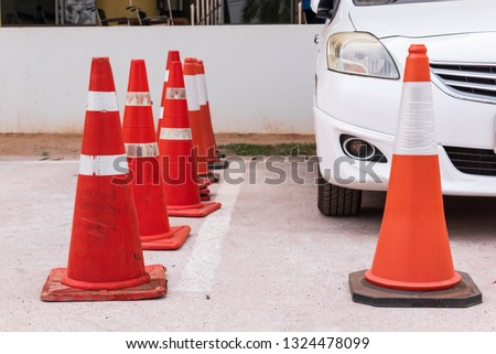 Plastic signaling traffic cone in the parking car.Orange cones used to close off area for VIP customer.Special guest zone.Safety zoning site concept. #1324478099