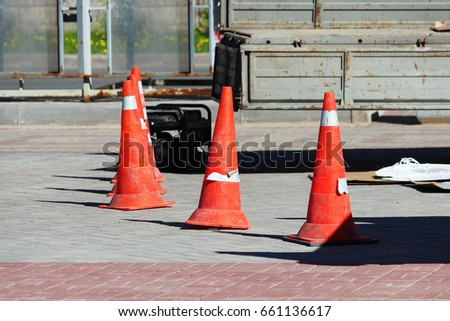 plastic signaling traffic Cones limit from people the place of installation of a glass advertising stand where the crane works #661136617