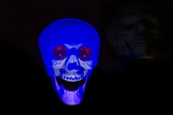 Plastic skull, with blue internal light. In the background, on the right, the shape of another skull. Black background.