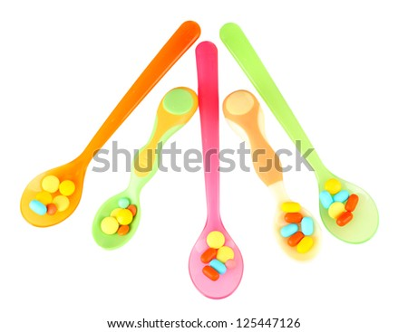 Plastic spoons with color pills, isolated on white