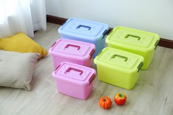 Plastic storage boxes stacked on the floor of the room