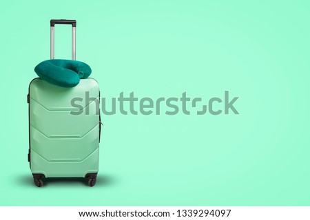 Plastic suitcase and travel pillow on a green background. Concept of travel, business trips, trips to visit friends and relatives