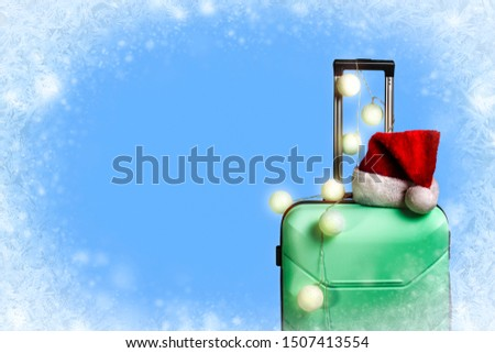 Plastic suitcase, Santa Claus cap and garland on a blue background with snow. Concept of travel, business trips, trips to visit friends and relatives on Christmas holidays. New Year's journey