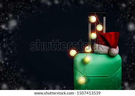 Plastic suitcase, Santa Claus cap and garland on a dark blue background with snow. Concept of travel, business trips, trips to visit friends and relatives on Christmas holidays. New Year's journey
