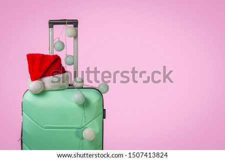 Plastic suitcase, Santa Claus cap and garland on a pink background. Concept of travel, business trips, trips to visit friends and relatives on Christmas holidays. New Year's journey #1507413824