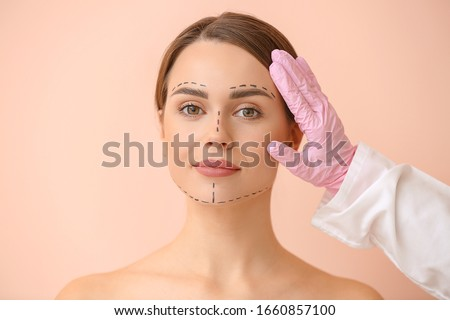 Plastic surgeon touching face of young woman on color background Foto d'archivio ©