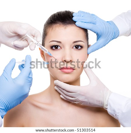 Plastic surgeons giving injection in female lips - isolated white