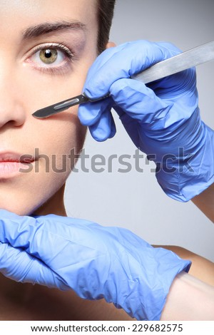 Plastic surgery, a woman in the clinic of aesthetic surgery.Caucasian woman during surgery using a scalpel