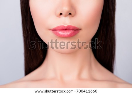 Plastic surgery concept. Lips filling, ideal and perfection mania. Cropped close up photo of young brunette woman`s lips on light background