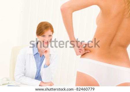 Plastic surgery consultation female doctor patient pinch skin on hips