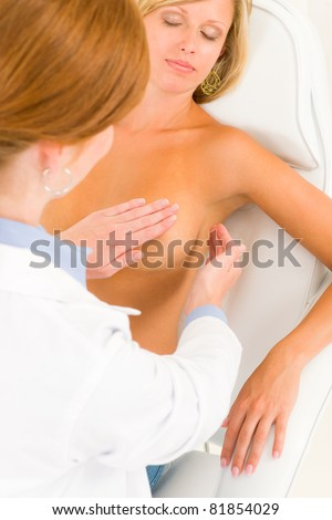 Plastic surgery female doctor examine blond woman patient breast shape