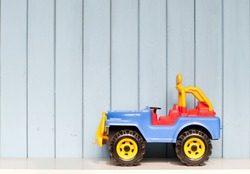 plastic toy car jeep on the bookshelf in children's room on blue wooden background