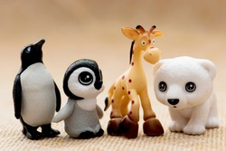 Plastic toy figurines. Penguins, giraffe and white teddy bear.