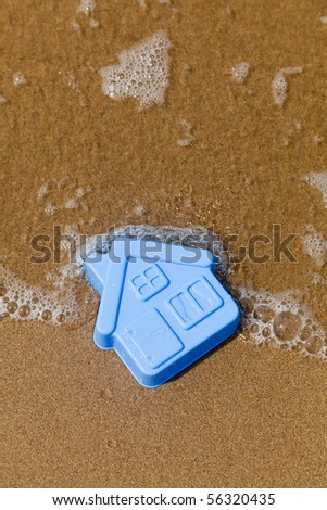 Plastic toy house lies on the sand