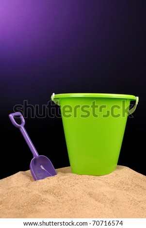 Plastic toy shovel and bucket in sand
