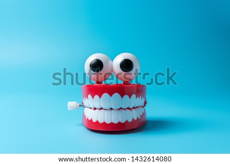 Plastic toy teeth on blue background. Abstract minimal composition.
