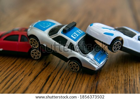 Plastic toys representing a car collision. 3 car pile up, crash, damage, insurance claim, injury, drunk driving, safety whilst driving, bad drivers, danger, caution concept background. Stock photo ©