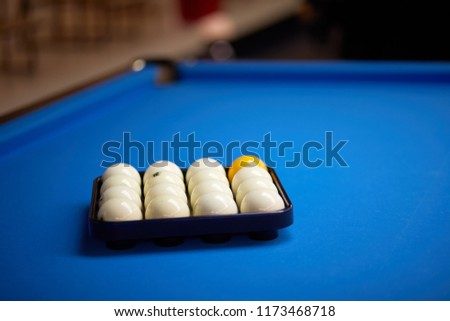 Plastic tray with billiard balls set on pool table.