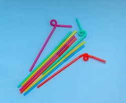 Plastic tubules for drinks on a blue background. Children's party with cocktails. The concept of environmental pollution by plastic, ecology.