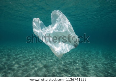 Plastic waste underwater, a plastic bag in the Mediterranean sea between water surface and a sandy seabed, Almeria, Andalusia, Spain