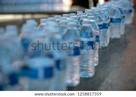 Plastic water bottles lined up in large quantity for single use.