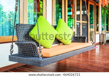 Plastic wicker porch swinging bench with green pillows and orange seat. #464026721