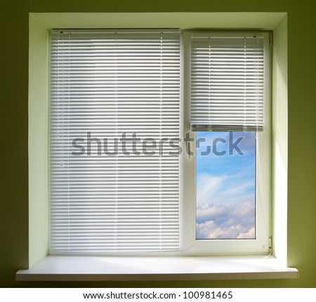 Plastic window blinds in the office with green walls.