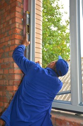 Plastic window installation: A professional window installer is checking with a spirit level if the window frame is installed evenly.