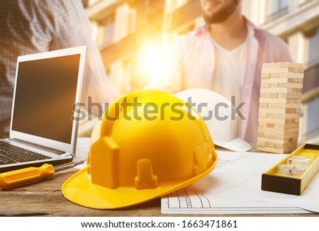 Plastic yellow safety helmet on a workplace desk stock photo