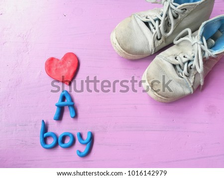 Plasticine clay dough made are cute red heart, blue a boy text and boys sneakers on pink background,  lovely wallpaper #1016142979