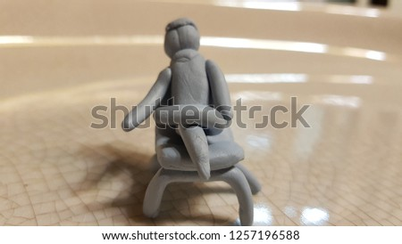 plasticine doll sitting with crossed feet to rest #1257196588