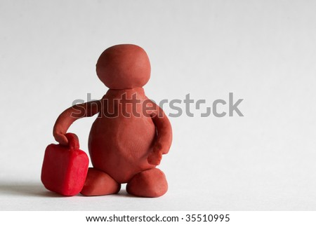 Plasticine man with a red suitcase over grey background