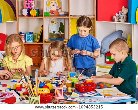 Plasticine modeling clay in children class. Teacher teaches kids together play dough and mold from plasticine in kindergarten or preschool. Group of four people. Learning in game.