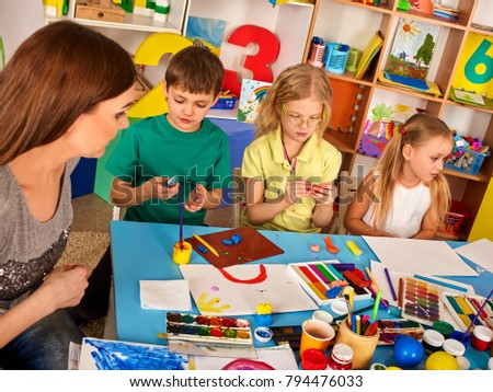 Plasticine modeling clay in children class. Teacher teaches kids together play dough and mold from plasticine in kindergarten or preschool. Group of four people. Newcomer in children\'s team.