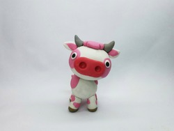 Plasticine statue of cute pink cow character on a white background.