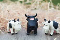 Plasticine world - little homemade black-and-white cows and black bull with red eyes stand on a farm on background of hay, selective focus