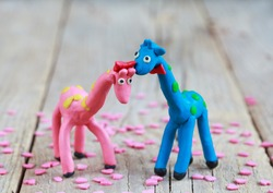 Plasticine world - little homemade blue giraffe with green spots and pink giraffe with orange spots with pink hearts on a wooden background, selective focus and place for text