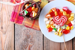 Plate and basket with colorful sweet candies. Copy space background. Selective focus. Traditional candies for Seker Bayram holiday