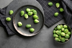 Plate and bowl with fresh raw brussel sprouts on cooking table