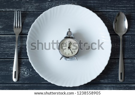 Plate and clock, it's time to eat. Spoon and fork for food. Top view.  #1238558905