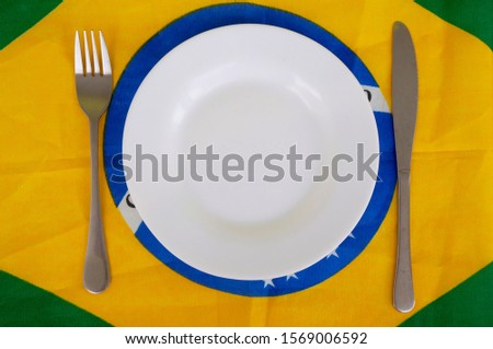 Plate and cutlery on Brazilian flag. Brazilian food concept. Cuisine of Brazil.