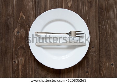 Plate and cutlery on wooden background in excelent form