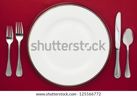 Plate and silverware on a red background - stock photo