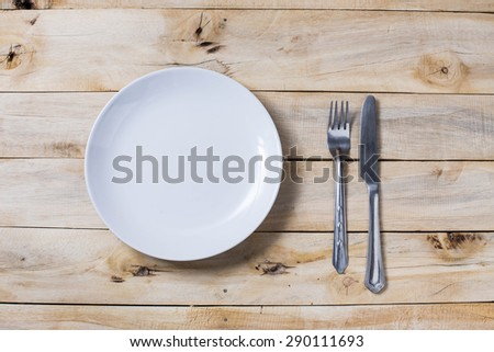 plate and silverware over white wooden background, View from above,on top