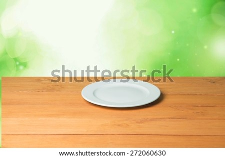 Plate. Empty plate on wooden table over nature background