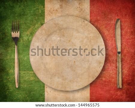 plate, fork and knife on grunge italian flag