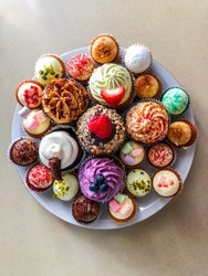 Plate full of  colorful cupcakes, top view