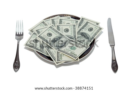 Plate full of dollars with knife and fork on each side - stock photo